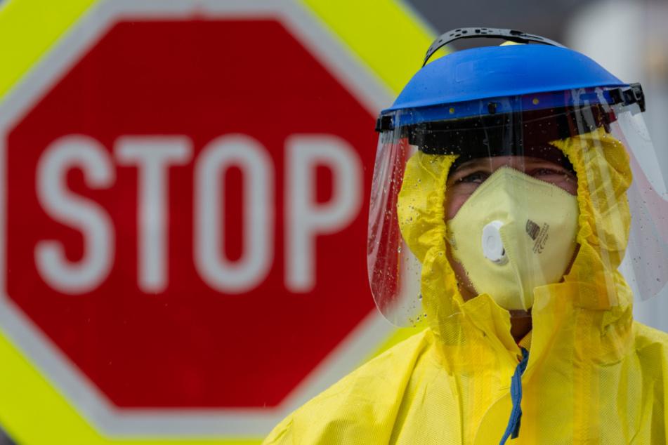 Ein Feuerwehrmann steht in Schutzbekleidung während einer Kontrolle von Reisenden an einer Tankstelle der Autobahn D8 Dresden - Prag vor einem Stopschild.