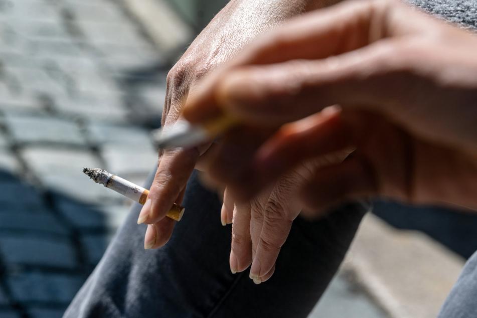 Raucher halten eine brennende Zigarette in der Hand. Die WHO verweist darauf, dass Rauchen das Risiko einer schweren Covid-19-Erkrankung erhöht.