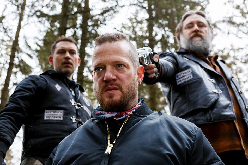 """Biker Bert Groll (Aurel Manthei, vorn) in Todesangst: Bandenchef Andy (Nicki von Tempelhoff, r.) und Ricky (Julian Schmieder) möchten """"die Ratte"""" erledigen. Aber wieso?"""
