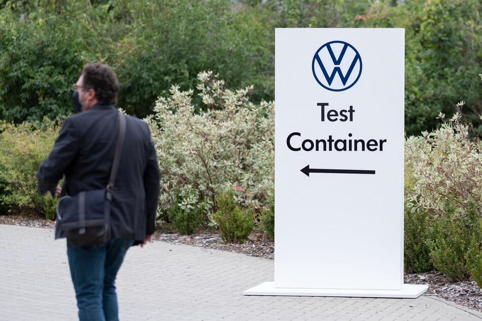 Ein Hinweisschild zum Coronatest-Container ist auf dem Werksgelände der Volkswagen AG zu sehen.