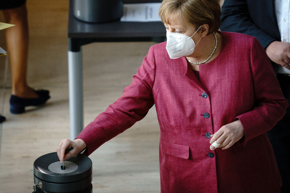 Bundeskanzlerin Angela Merkel steckt ihre Stimmkarte bei der Sitzung des Bundestags in die Wahlurne. Am 21. April wurde über das erweiterte Infektionsschutzgesetz zur Eindämmung der Corona-Pandemie abgestimmt.
