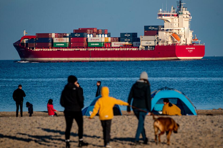 Strandspaziergänger schauen auf einen Containerfrachter. (Symbolbild)