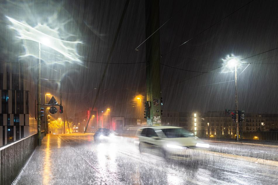 Zwei Autos fahren während Starkregen und Gewitter über eine Straße. Nordrhein-Westfalen wurde in der Nacht von teils schweren Gewitter getroffen. In den benachbarten Niederlanden hatten Unwetter bereits erhebliche Schäden angerichtet.