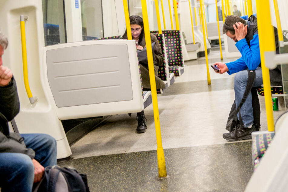 Ein Mann (l.) hustet in einem fast leeren Londoner U-Bahnwagen. (Symbolbild)