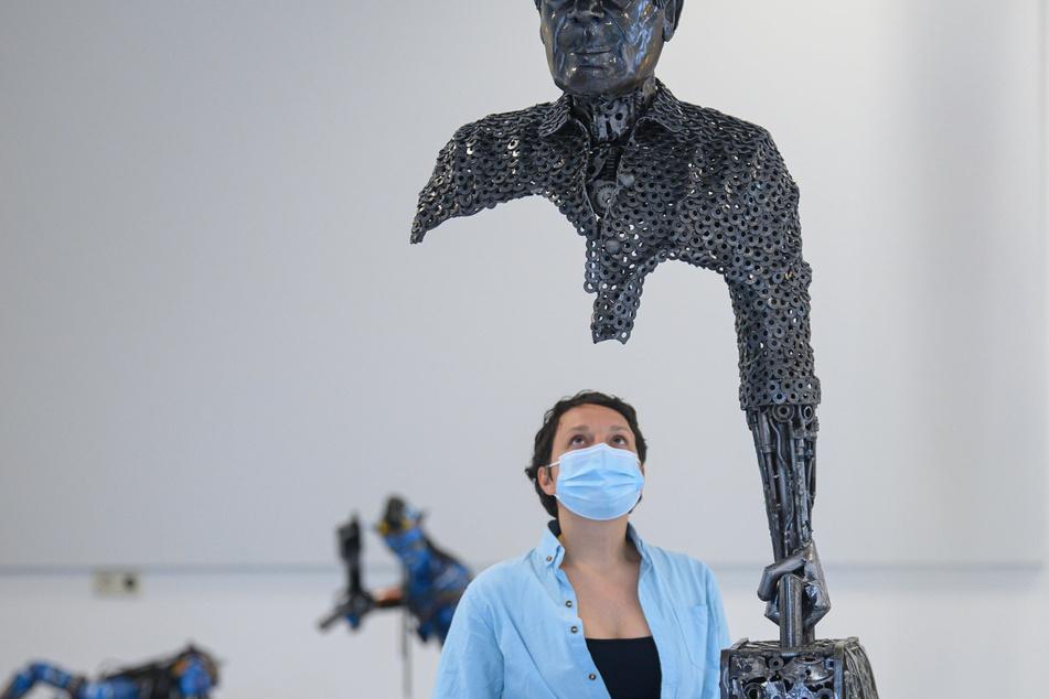 """Luisa Mac Donnacha betrachtet die überdimensional große Skulptur """"Der Reisende""""."""