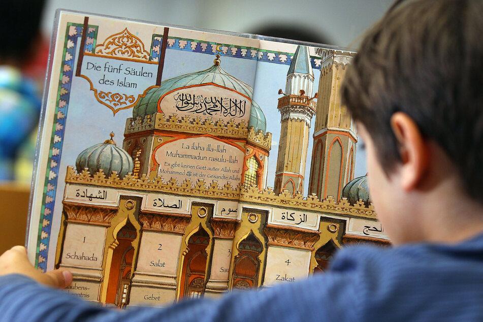 Ein Junge liest während des islamischen Religionsunterrichts in einem Schulbuch.
