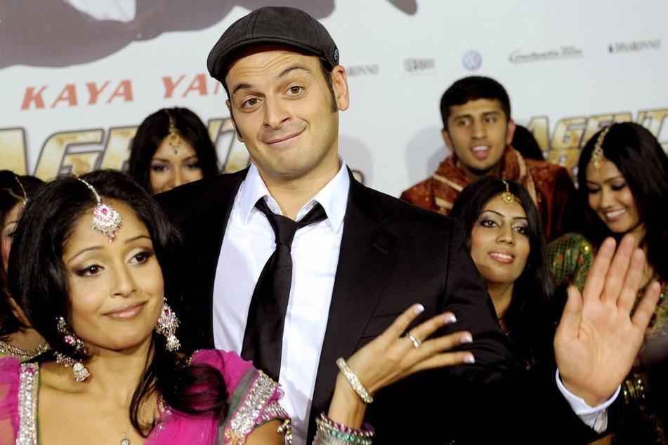"""Kaya Yanar (M.) posiert am 17. Oktober 2012 bei der Premiere des Kinofilms """"Agent Ranjid rettet die Welt"""" in Köln zusammen mit Tänzerinnen."""