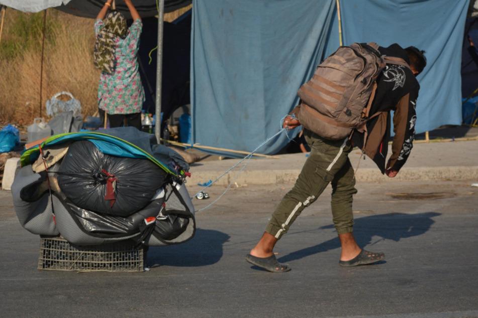 Ein Migrant trägt einen Rucksack und zieht seine Habseligkeiten hinter sich her.