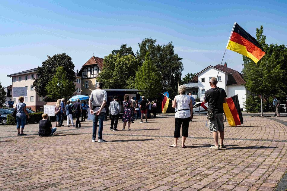 Einige Anhänger und Parteimitglieder der AfD Oder-Spree stehen auf dem Marktplatz der brandenburgischen Gemeinde Grünheide und protestieren gegen den geplanten Bau der Tesla-Fabrik.