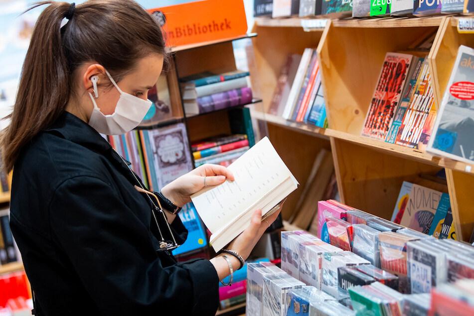 Eine Frau stöbert in einer Buchhandlung und trägt dabei einen Mundschutz. (Symbolbild)