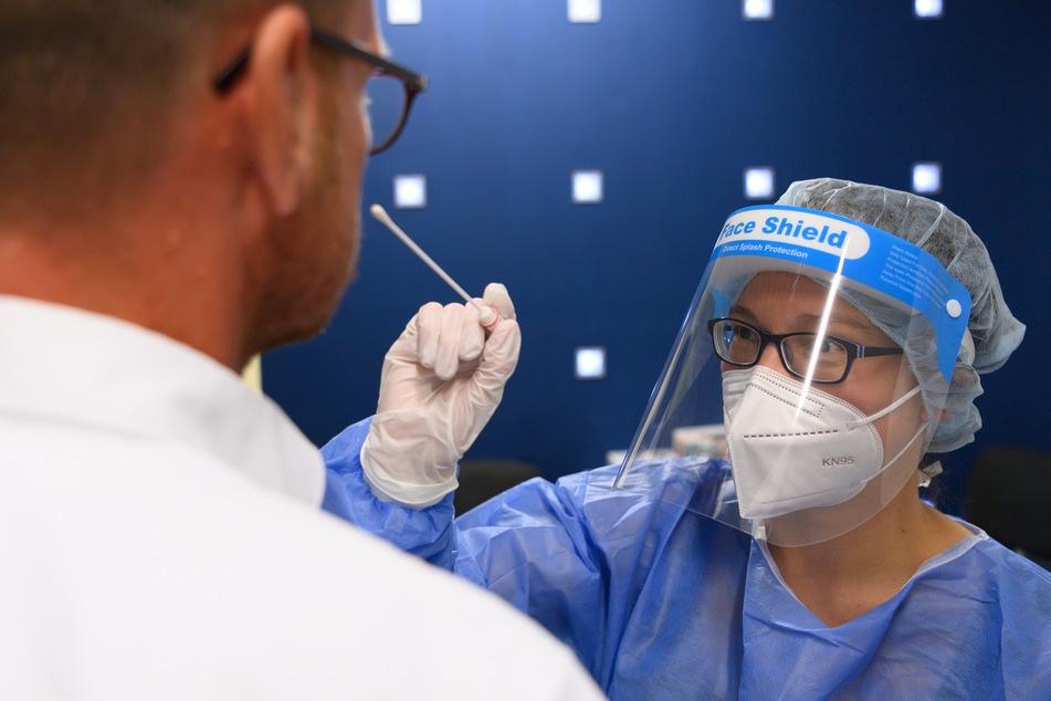 Ein Reisender lässt sich in der Corona-Teststation am Flughafen Dresden International auf das Coronavirus testen.