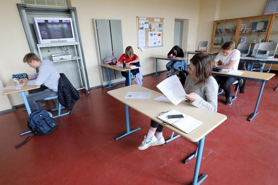 Schüler lernen in einer Schule unter dem notwendigen Corona-Abstand.