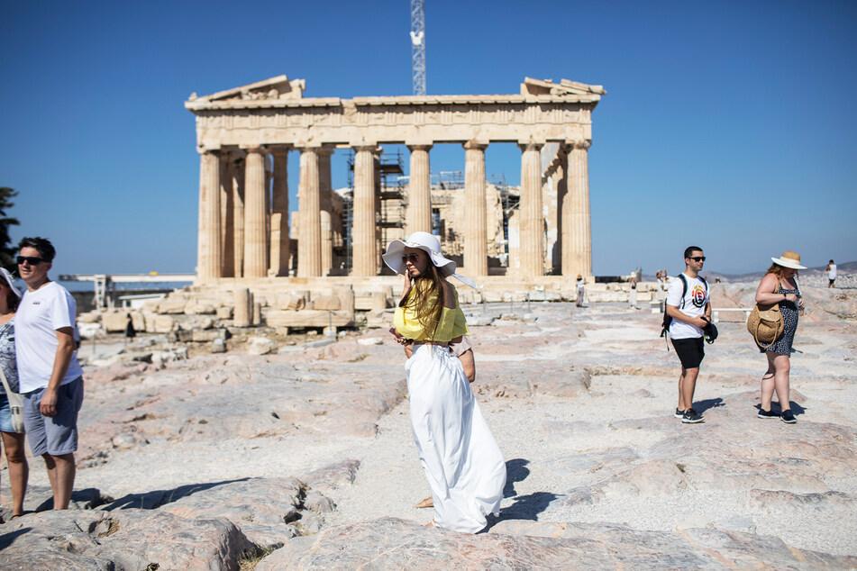 Touristen spazieren über die Athener Akropolis.