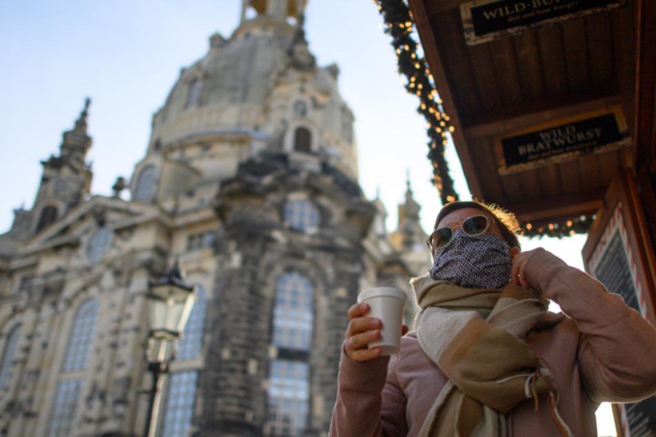 Eine Frau hält auf dem Neumarkt vor der Frauenkirche einen Becher Glühwein in der Hand. Steigt der Inzidenz-Wert über 200, ist der Glühweinverkauf in Dresden verboten.