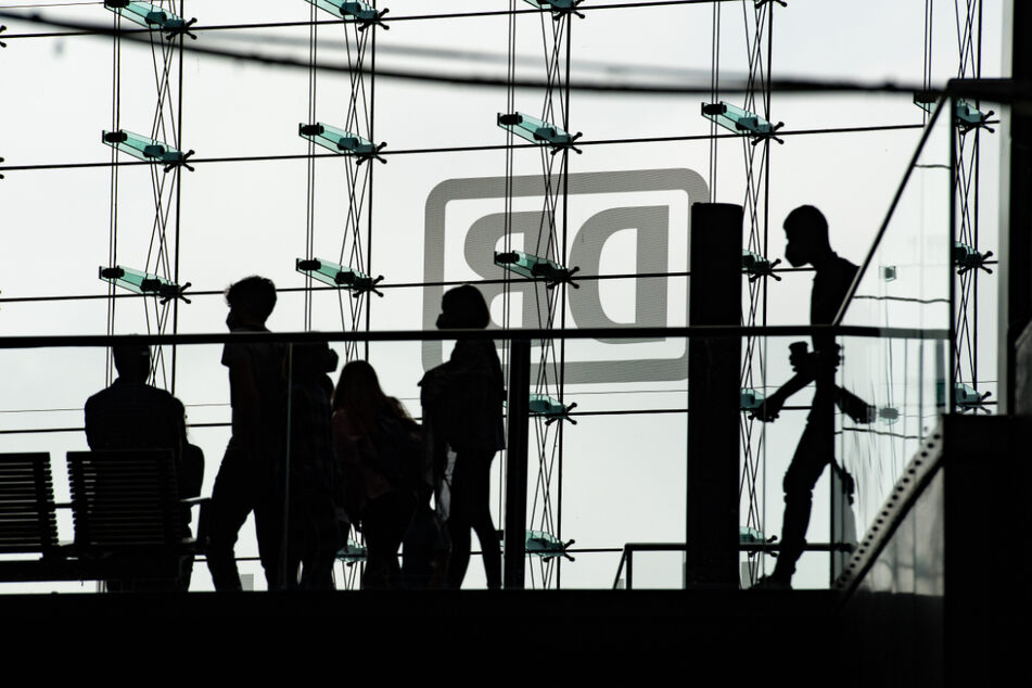 Bahnreisende sind nur als Silhouetten in der Glasfassade zu sehen. Die Deutsche Bahn streikt mehrere Tage. Viele Züge stehen still.