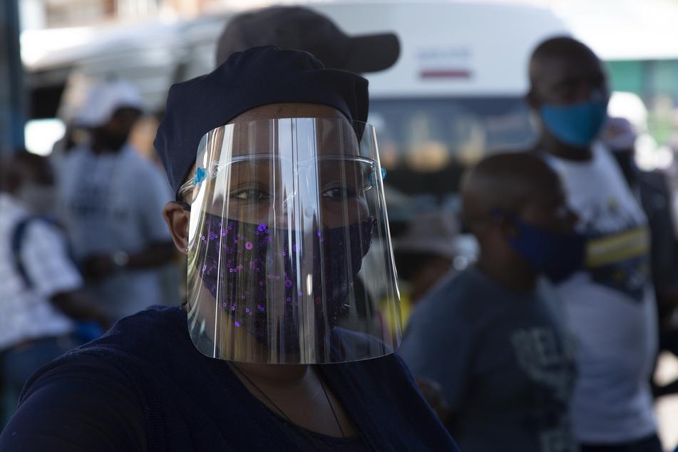 Südafrika, Johannesburg: Eine Frau, die eine Schutzbrille, einen Mund-Nasen-Schutz und ein Gesichtsvisier trägt, steht vor dem Hauptbahnhof.