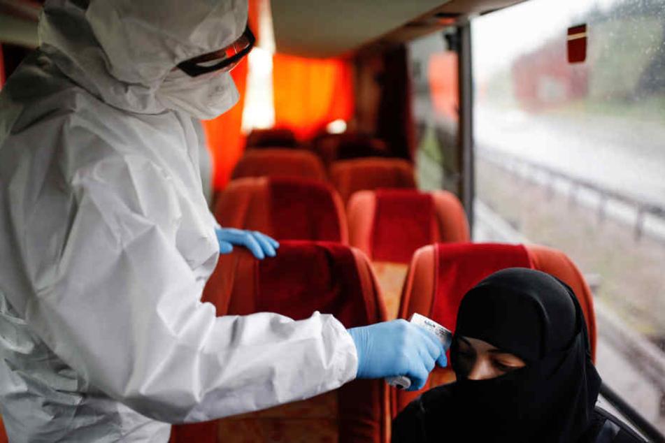 Istanbul: Ein medizinischer Mitarbeiter im Schutzanzug misst in einem Bus die Körpertemperatur einer Frau.