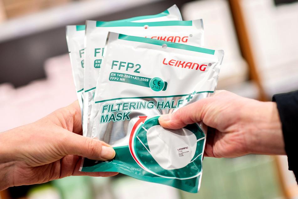 Eine Apothekerin gibt einer älteren Kundin mehrere FFP2-Atemschutzmasken.