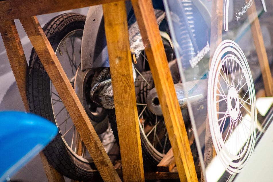 Die Motorrad-Teile befinden sich in einem Holzgestell.