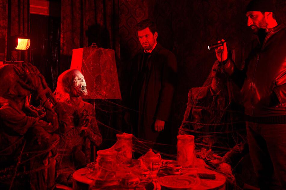 Grausiger Fund: In einem geheimen Zimmer finden die Kommissare diesen bizarren Tatort vor. In dem dunklen Raum steht ein Tisch, der zum Kaffee gedeckt ist. Teller, Tassen und Kannen sind mit Spinnweben bedeckt. Um den Tisch sitzen drei mumifizierte Tote, denen die Geschlechtsorgane entfernt wurden.