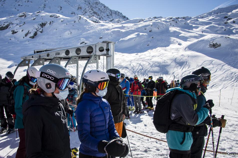 Skifahrer mit Gesichtsmasken stehen am Eröffnungstag des Skigebiets Verbier in den Schweizer Alpen in einer Schlange für den Sessellift an.