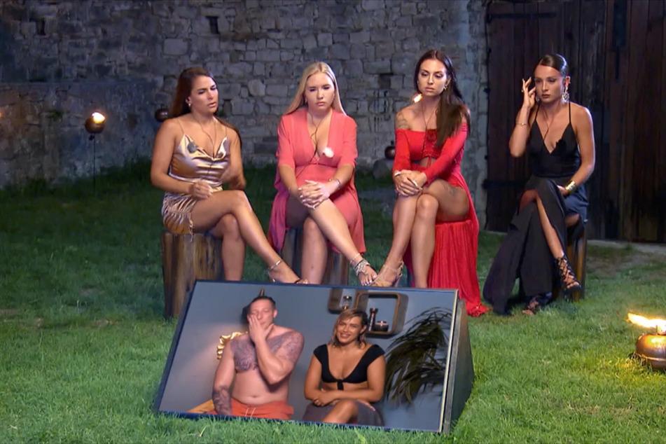 Meike (29, v.l.n.r.), Marlisa (31), Sabine (28) und Alicia (26) schauen Sabines Freund Mike (28) beim Lagerfeuer dabei zu, wie er sich allmählich in Verführerin Gina (23) verliebt.