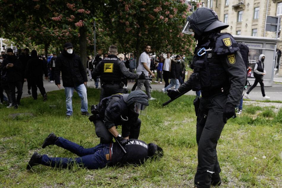 Die Polizei nimmt einen Protestler fest.