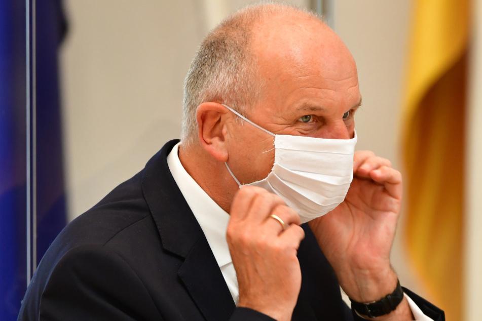 Dietmar Woidke (SPD), Ministerpräsident von Brandenburg, legt sich während der Sitzung des Brandenburger Landtages einen Mund-Nasenschutz an.