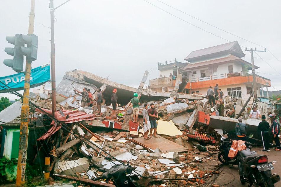 Anwohner begutachten die beschädigten Gebäude.