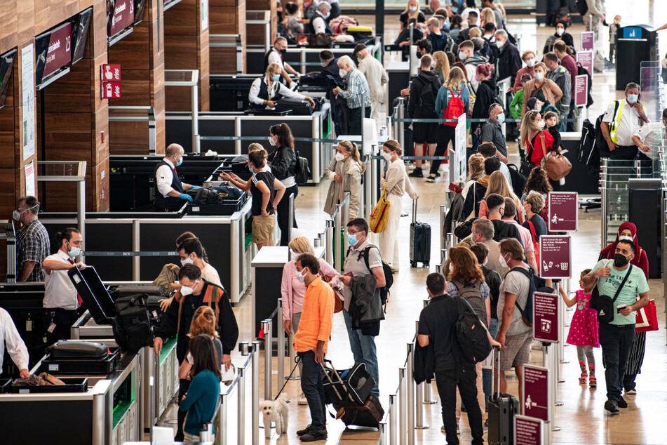 Reisende stehen am Flughafen BER am Security Check. Ein Grund für die stark ansteigende Inzidenz in Berlin könnte die Reisewelle während der Ferienzeit sein.