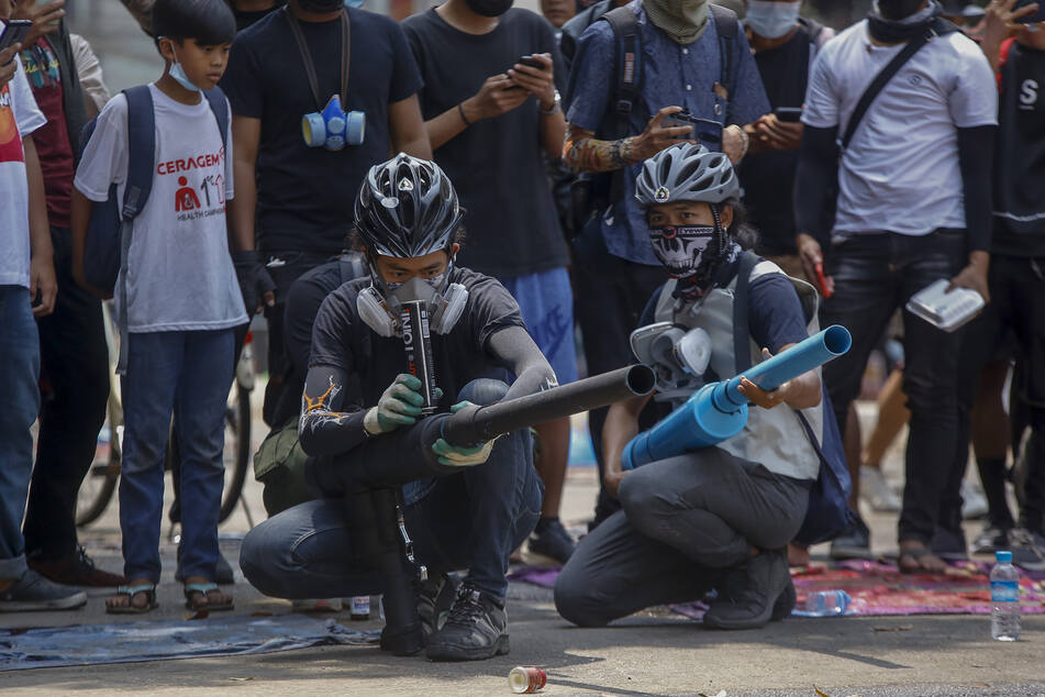 Demonstranten testen selbstgebaute provisorische Waffen bei einem Protest gegen den Militärputsch.
