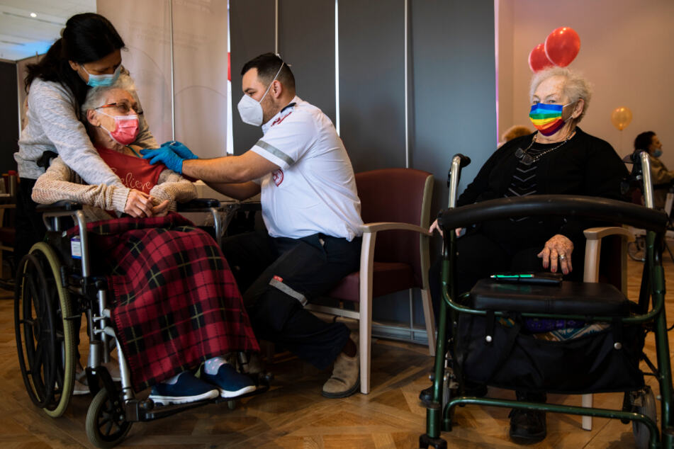 """Netanja: Eine israelische Frau erhält in einem privaten Pflegeheim von einem Freiwilligen der nationalen Hilfsorganisation """"Magen David Adom"""" ihre zweite Dosis des Corona-Impfstoffs von Pfizer/Biontech."""