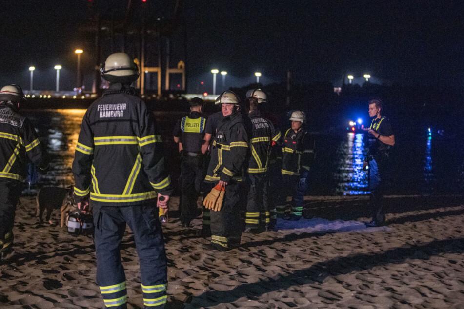 Feuerwehrleute sind am Elbstrand in Övelgönne im Einsatz.