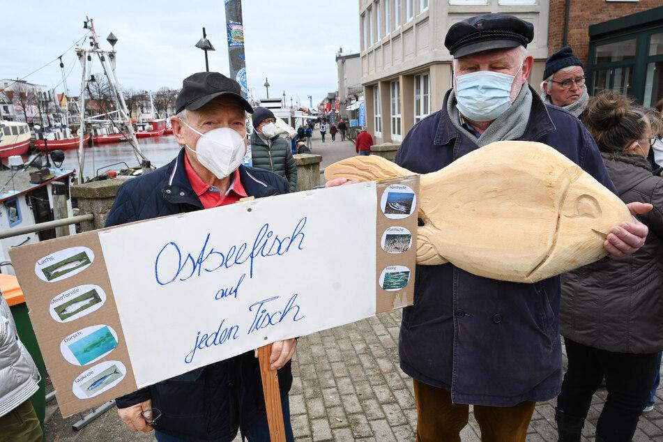 """Ein Gegendemonstrant aus Warnemünde hält ein Plakat mit der Aufschrift """"Ostseefisch auf jeden Tisch""""."""