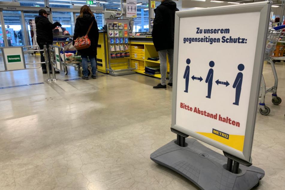 Ein Hinweisschild bittet die Kunden in einem Großmarkt der Metro AG im Kassenbereich Abstand zum nächsten Kunden zu halten.