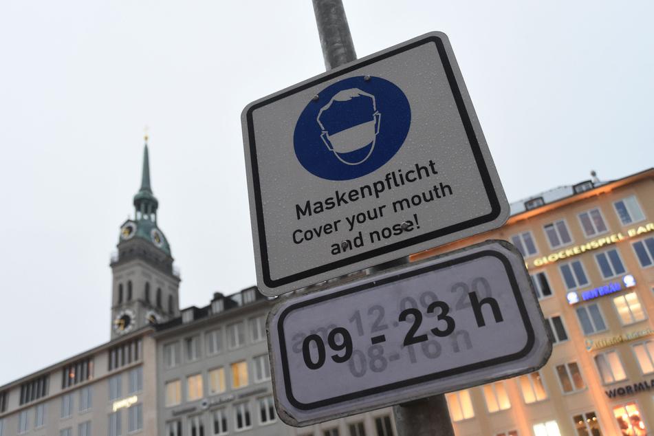 """Ein Schild mit der Aufschrift """"Maskenpflicht"""" ist am Marienplatz vor dem Alten Peter an einem Mast angebracht."""