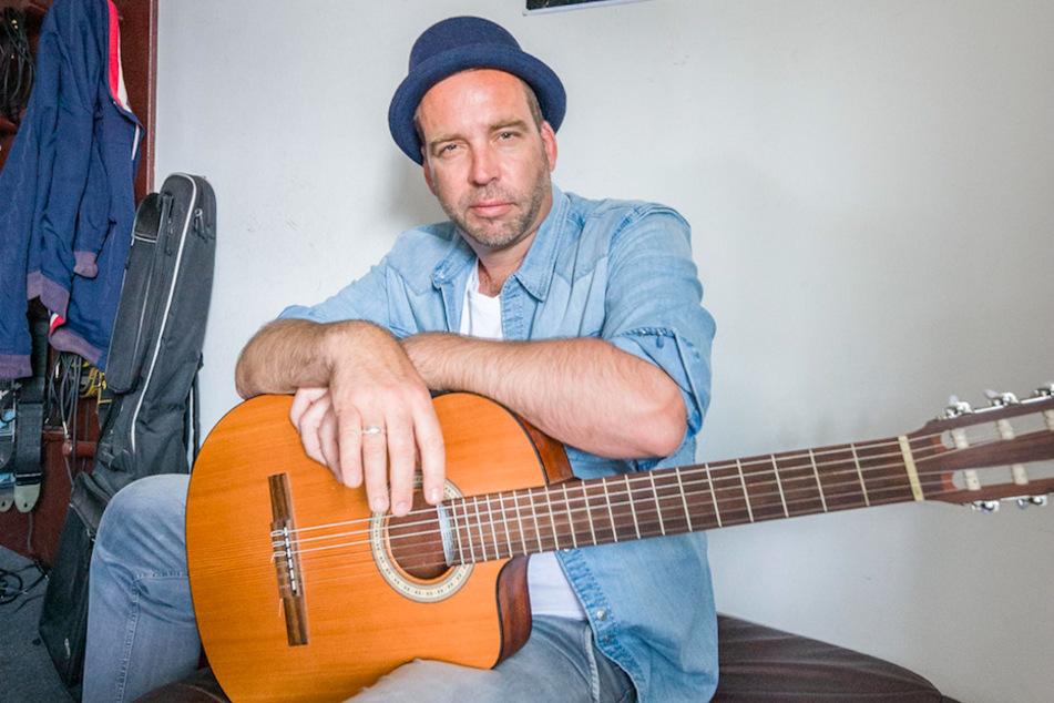Jan Gott (45), Musiker, sitzt mit einer Gitarre in seinem Wohnzimmer. Der gebürtige Münchner begann mit 13 Jahren, Gitarre und Klavier zu spielen.