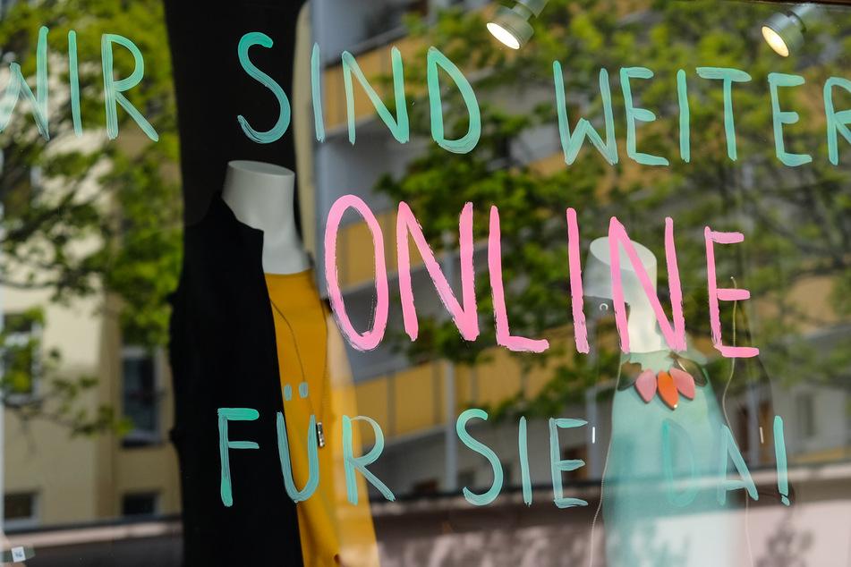 """""""Wir sind weiter online für sie da!"""" steht während der Coronakrise an der Schaufensterscheibe eines Modegeschäfts."""