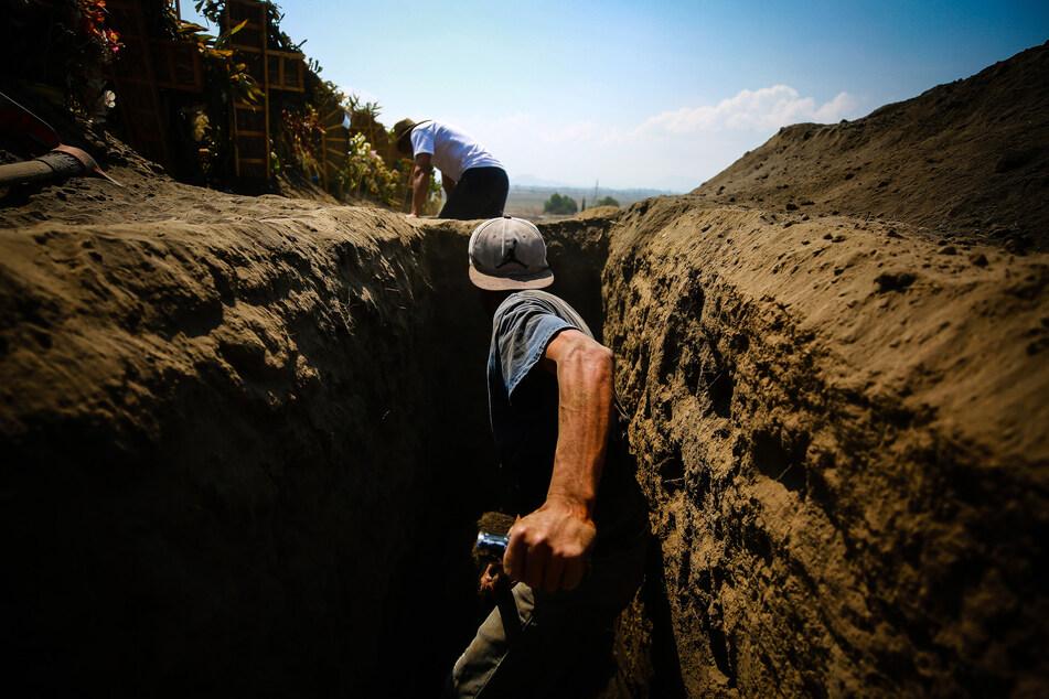 Ein Arbeiter hebt in einem Bereich des Friedhofs von Xico ein Grab aus. (Symbolbild)