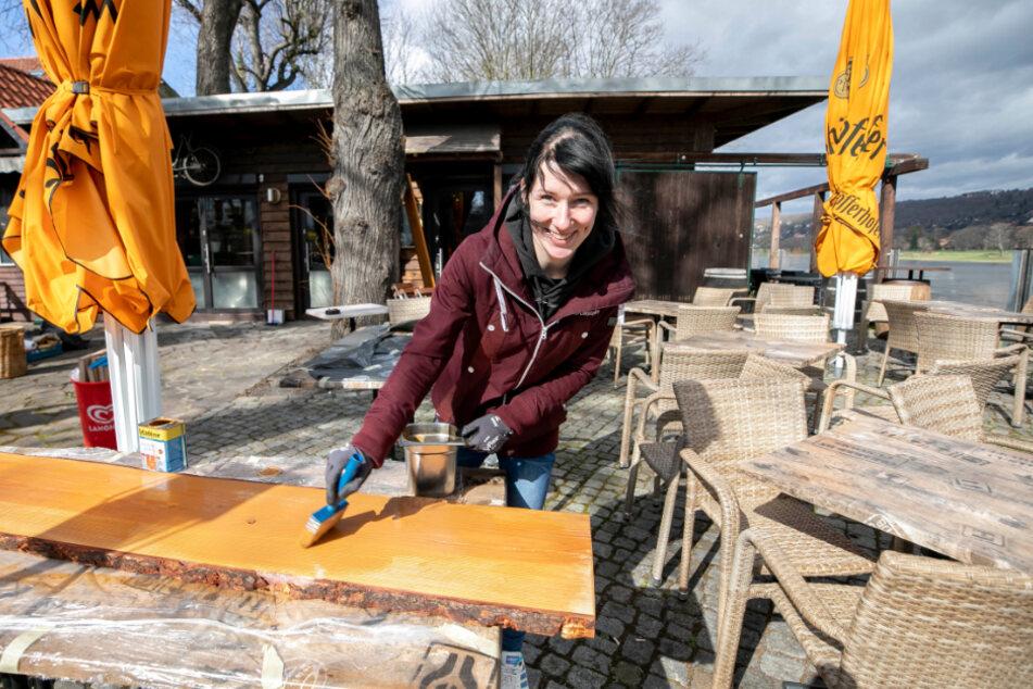 Service-Mitarbeiterin Vanessa Müller (25) ölt die neuen rustikalen Regalbreter ein, auf denen bald Biergläser stehen.