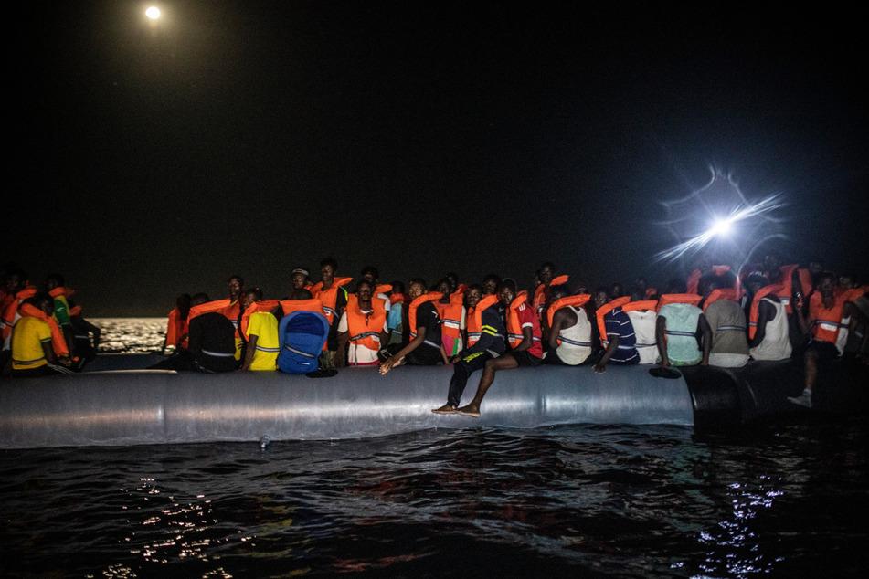 """Migranten warten in einem Schlauchboot darauf an Bord des Rettungsschiffes """"Louise Michel"""" aufgenommen zu werden."""