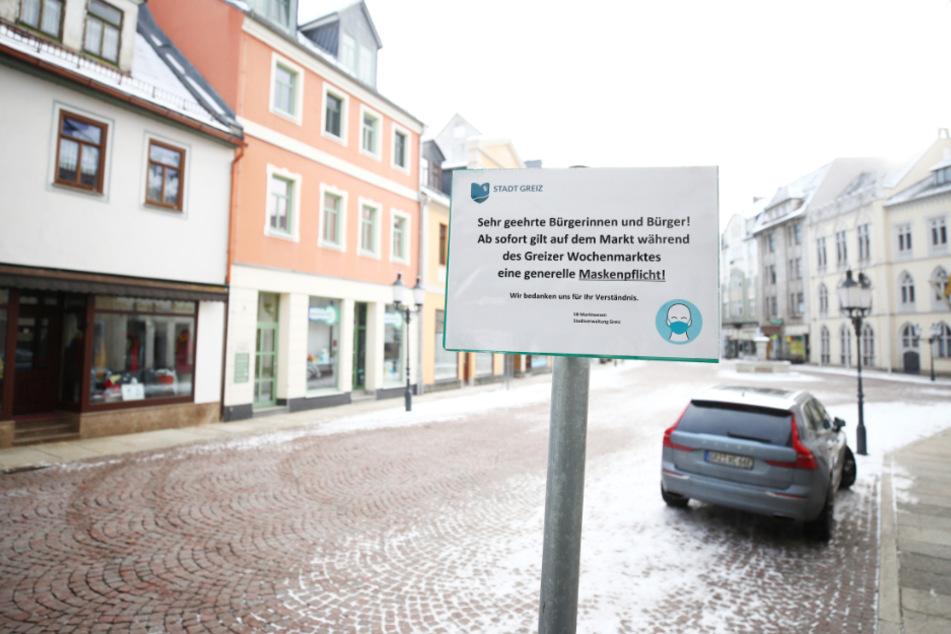 Das Hinweisschild zur Maskenpflicht auf dem leeren Marktplatz im thüringischen Greiz.