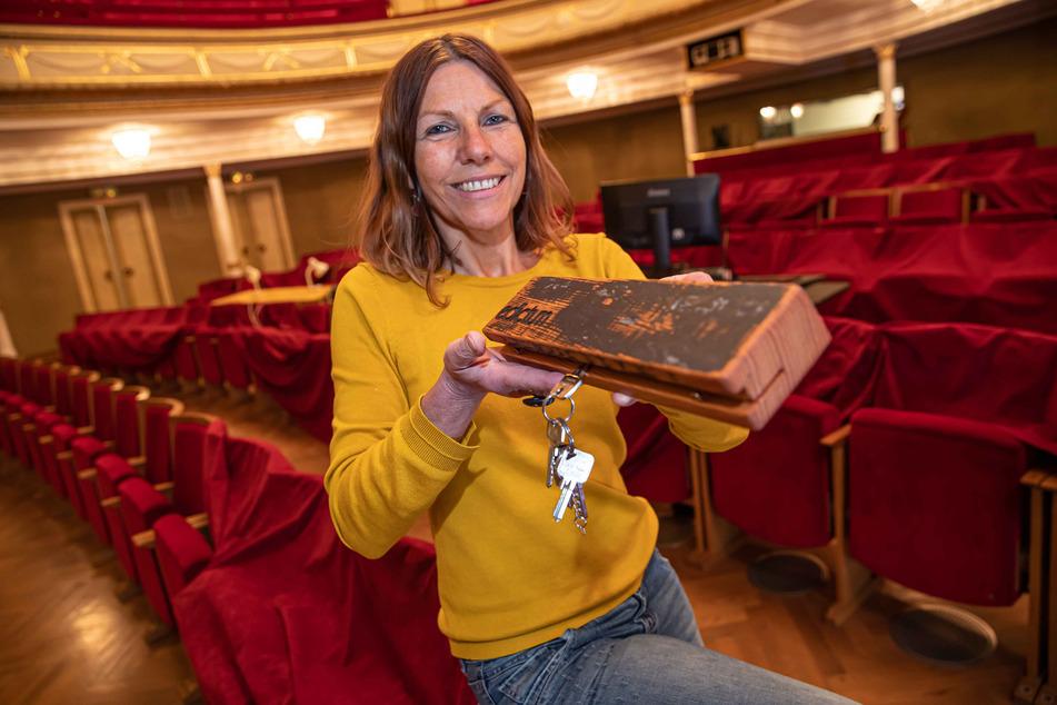 Carolin Eschenbrenner vom Theater Plauen-Zwickau zeigt ein Schlüsselbrett, das aus dem Bühnenboden gefertigt wurde.