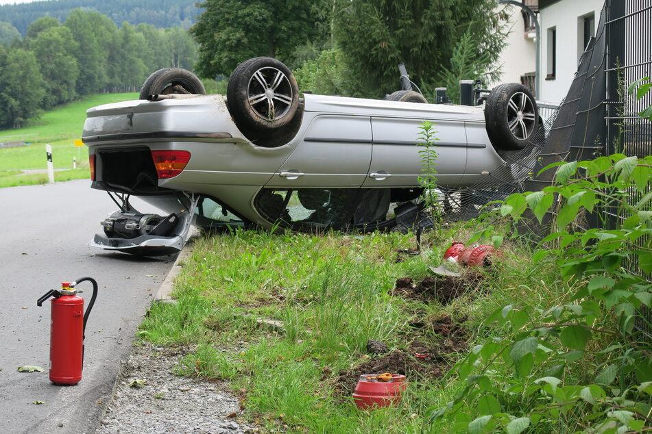 Gartenzaun-Crash im Erzgebirge! Ein BMW-Fahrer landete am Montag mit seinem Wagen auf dem Dach und beschädigte dabei einen Zaun eines Einfamilienhauses.