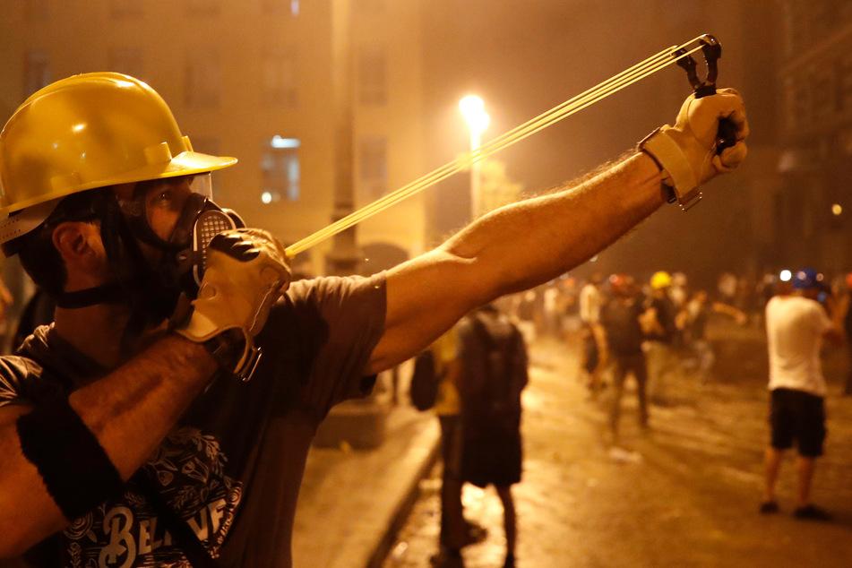 Ein Protestierender schleudert mit einer Schleuder gegen die libanesische Bereitschaftspolizei, während eines regierungskritischen Protests.