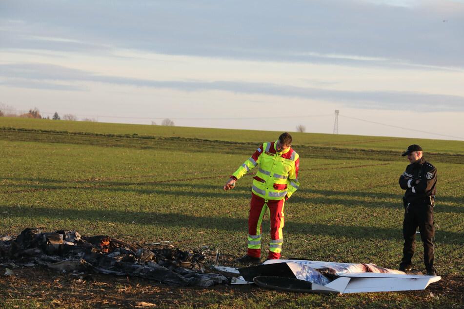 Einsatzkräfte von Polizei und Feuerwehr stehen nach dem Absturz eines Kleinflugzeuges an der Unfallstelle.