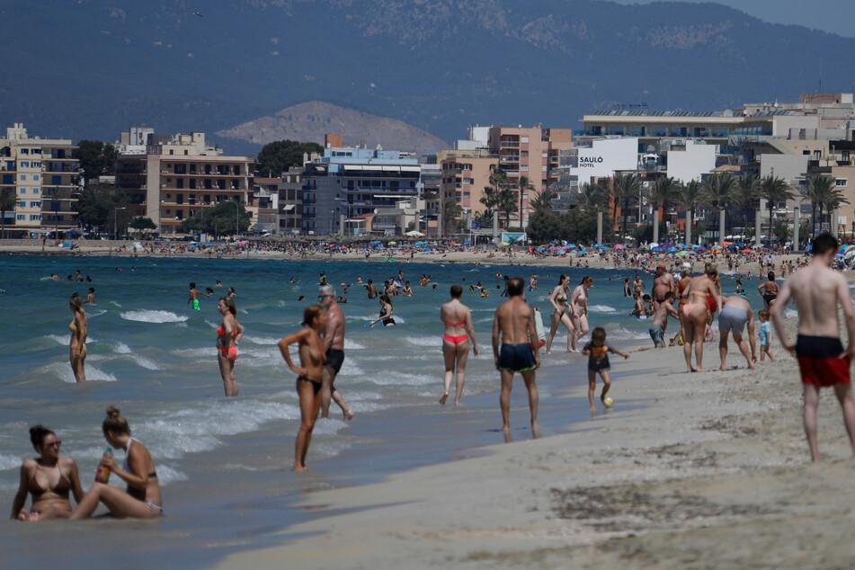 Touristen sonnen sich am Strand von Arenal. Die Maskenpflicht wurde in Spanien erheblich gelockert. Mund-Nasen-Schutz muss im Freien nicht mehr immer und überall getragen werden.