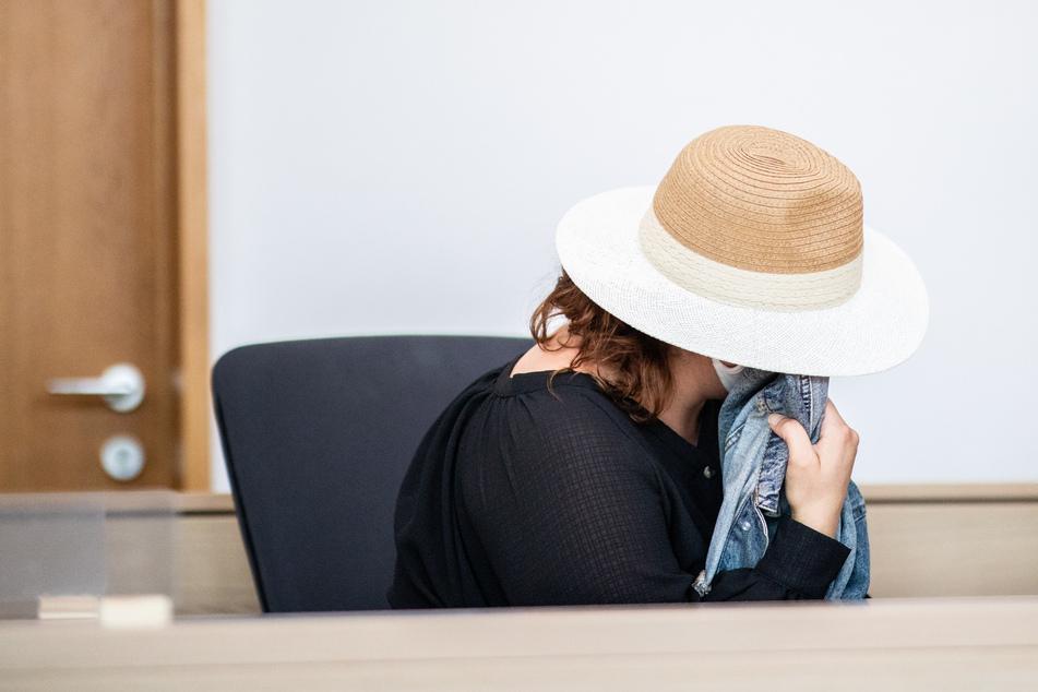 Die Angeklagte sitzt mit einem Hut auf dem Kopf und einer Jacke vor dem Gesicht im Gerichtssaal in Krefeld.