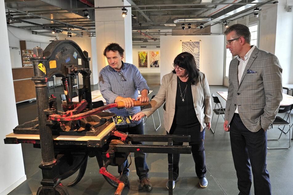 Galerie-Direktor Mathias Lindner, Gabriele Martin (62) vom Kulturbetrieb der Stadt und Bürgermeister Ralph Burghart (50, CDU) probieren im Tietz eine alte Druckpresse aus.