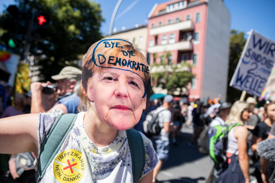 """Eine Frau trägt eine Merkel-Maske mit der Aufschrift """"Bye bye Demokratie"""" auf der Demonstration gegen die Corona-Beschränkungen."""